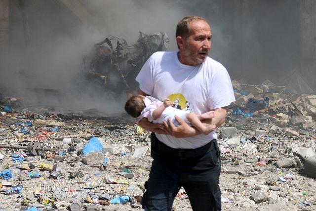 fot: Reuters Mężczyzna wynosi dziecko ze zbombardowanych budynków w syryjskim Aleppo. [źródło: PISM]